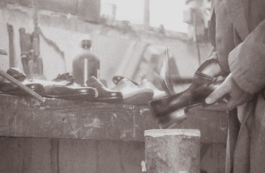 Craftsman shoemaker at work on a historic company photo shoe